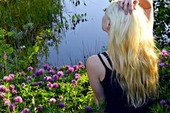 Sedendosi su un tappeto floreale del trifoglio vicino alla foresta di una ragazza bionda del piccolo lago Fotografie Stock