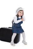 Sedendosi su una ragazza della valigia chiama dal telefono Fotografie Stock