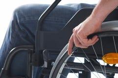 Sedendosi su una sedia a rotelle Fotografia Stock