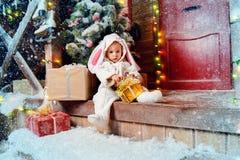 Sedendosi sul ragazzo del coniglio del portico fotografia stock