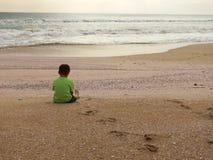 Sedendosi sulla spiaggia Immagini Stock Libere da Diritti
