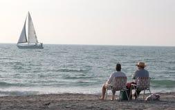 Sedendosi sulla spiaggia Fotografia Stock