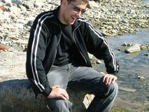Sedendosi sulla spiaggia Immagini Stock