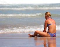 Sedendosi sulla spiaggia Fotografie Stock