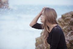 Sedendosi sulla spiaggia Immagine Stock