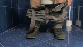 Sedendosi sulla toilette stock footage