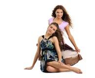 Sedendosi sulle ragazze del pavimento Immagine Stock