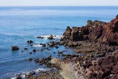 Sedendosi sulle rocce Immagini Stock