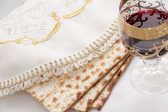 Seder, passover holiday. Matzen lying on the plate covered with bestrikten napkins, wine glass with red wine, close-up Stock Photo