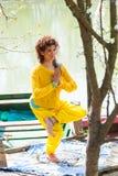 Sedere di yoga di pratica della giovane donna il colpo pieno del corpo di posa dell'equilibrio di giorno soleggiato del lago immagini stock