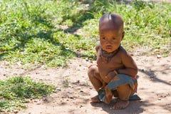 Sedi del ragazzo di Himba sulla terra. Fotografia Stock Libera da Diritti