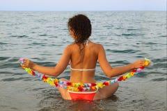 Sedi della donna in acqua sul mare Immagine Stock