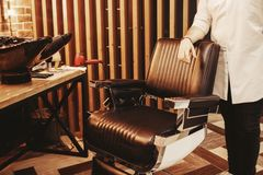 Sedia alla moda del parrucchiere del cliente Negozio di barbiere per gli uomini fotografie stock