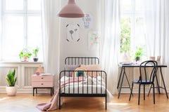 Sedia allo scrittorio accanto al letto nell'interno rosa e bianco della stanza del ` s della ragazza con le piante e le finestre immagini stock