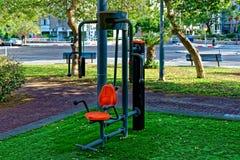 Sedia arancio di esercizio pubblico con la struttura grigia e le maniglie di sostegno allegate ad un palo nero immagine stock