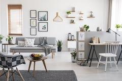 Sedia bianca allo scrittorio nell'interno spazioso dell'appartamento con la galleria sopra il sofà grigio vicino alla finestra Fo fotografia stock libera da diritti