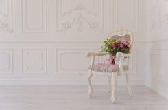 Sedia bianca con il bouqet del fiore che staing nell'angolo dello studio Fotografie Stock