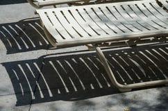 Sedia bianca della chaise-lounge della spiaggia con le ombre scure dalle stecche Fotografie Stock
