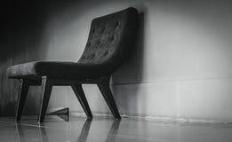 Sedia classica nera con progettazione unica in toilette vuota vicino al muro di cemento su fondo scuro e drammatico Una poltrona  fotografia stock