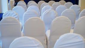 Sedia con il lato posteriore del panno bianco della copertura in una fila in un grande corridoio per nozze, la conferenza o il se video d archivio