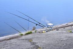 Sedia con le canne da pesca ed attrezzatura di pesca nel lago Fotografie Stock Libere da Diritti