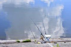 Sedia con le canne da pesca ed attrezzatura di pesca nel lago Fotografia Stock Libera da Diritti