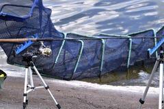 Sedia con le canne da pesca ed attrezzatura di pesca nel lago Immagini Stock Libere da Diritti