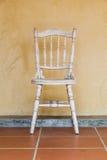 Sedia d'annata bianca vicino alla vecchia parete gialla fotografia stock