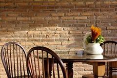 Sedia d'annata e tavola con il fiore Immagini Stock Libere da Diritti