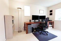 Sedia del computer alla grande tavola di lavoro con i monitor del computer ed altre attrezzature di tecnologia nell'interno lumin fotografia stock libera da diritti