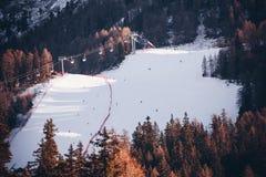 Sedia dell'ascensore di sci e degli sciatori con la vista delle montagne nevose delle alpi Fotografia Stock