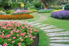 Sedia di Brown in un giardino di fiori con il passaggio pedonale Immagini Stock