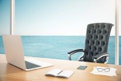 Sedia di cuoio moderna con la tavola di legno con il computer portatile nella sala con Fotografia Stock Libera da Diritti