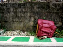 Sedia di cuoio rotta su un marciapiede Immagini Stock