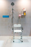 Sedia di doccia riempita con i braccioli e la parte posteriore in bagno con la t luminosa Fotografie Stock Libere da Diritti