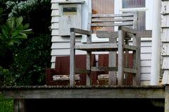 Sedia di legno davanti ad una casa bianca Fotografie Stock