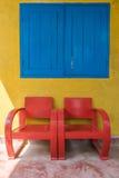 sedia di legno rossa e parete gialla con sole Fotografie Stock Libere da Diritti