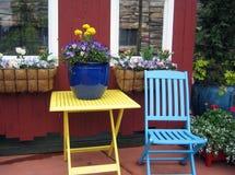 Sedia di legno variopinta e tavola con i fiori e le scatole di finestra fotografie stock libere da diritti