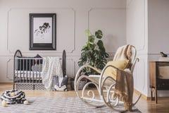 Sedia di oscillazione con la coperta ed il cuscino nella stanza alla moda del bambino fotografia stock libera da diritti