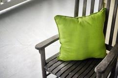Sedia di oscillazione di legno con il cuscino verde Fotografia Stock