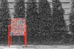 Sedia di plastica variopinta astratta del rattan di tessitura che sta sul pavimento di calcestruzzo Fotografia Stock
