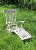 Sedia di salotto nel campo sfrenatamente sviluppato di erba Immagine Stock