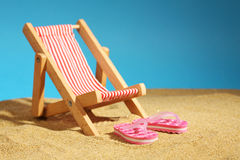 Sedia di spiaggia che sta sulla sabbia di mare e sui Flip-flop rosa con i fiori ed il cielo blu Immagine Stock Libera da Diritti