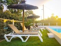 Sedia di spiaggia davanti a chiara acqua blu della piscina fotografia stock