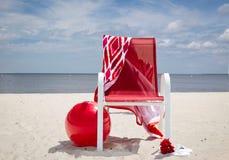 Sedia di spiaggia rossa sulla spiaggia con la grande palla rossa che si trova sulla sabbia Fotografie Stock