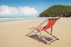 Sedia di spiaggia sulla spiaggia e sulla montagna con lo Sc del cielo blu e della nuvola Fotografia Stock