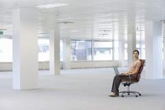 Sedia di Using Laptop On della donna di affari in ufficio Fotografie Stock