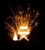 Sedia e megafono di Director's in stella filante d'ardore su fondo scuro Fotografia Stock