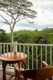 Sedia e tavola di legno per 1 persona in un balcone che trascura una f immagine stock libera da diritti