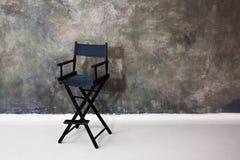 Sedia nera del ` s di direttore su fondo grigio Alta sedia pieghevole sui precedenti strutturati della parete Immagine Stock Libera da Diritti